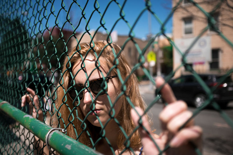 Young Woman Seen Through Chainlink Fence