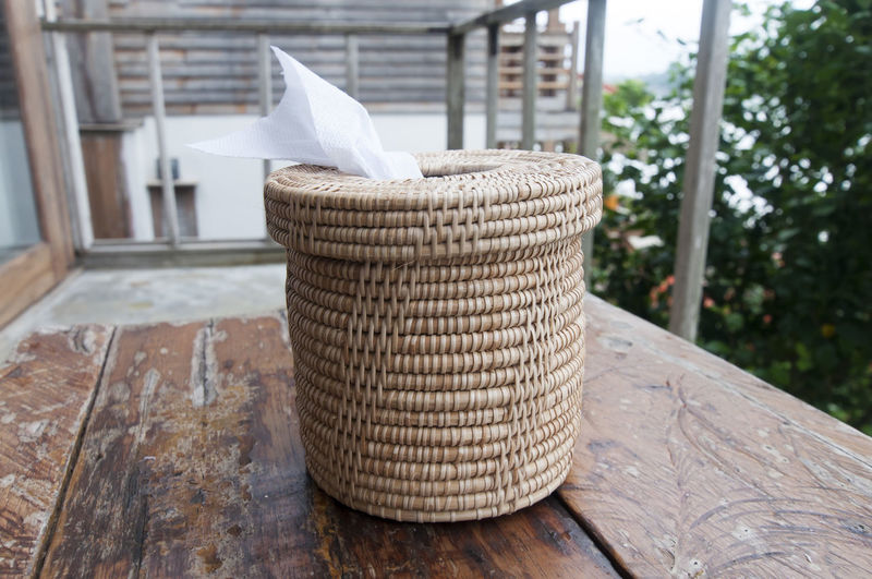Close-up of wicker tissue paper container on table