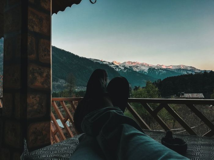 Low Section Of Person Sitting In Balcony Against Mountains During Sunset