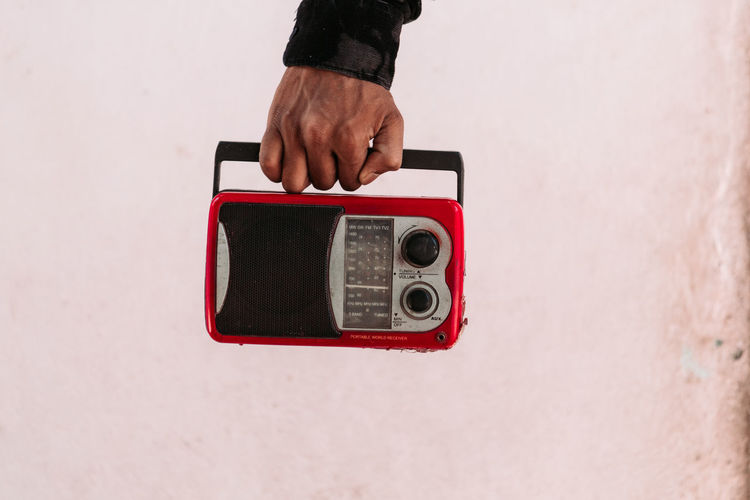 Cropped hand of man holding radio against wall