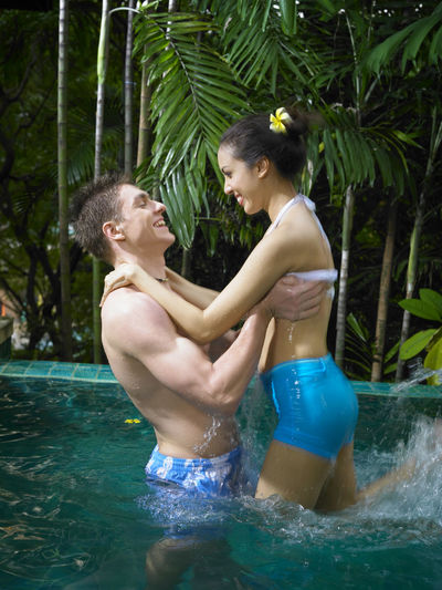 Young Couple Swimming In Pool