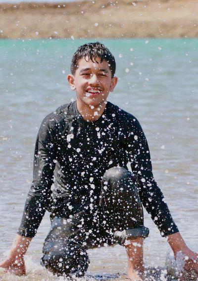 Smiling Teenage Boy Crouching On Shore At Beach