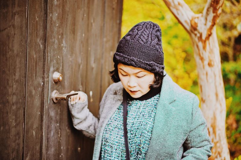 Woman in warm clothing standing against wooden door