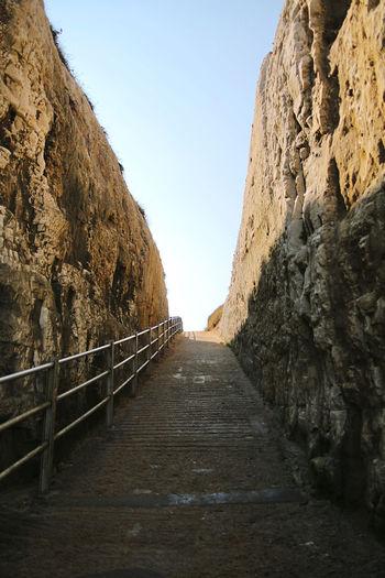 Footpath amidst rocks against clear sky