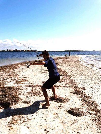 My grandson is enjoying a . getting ready to go Fishing Beauty In Nature Nature Sky One Person Full Length. Sand Leisure Activity. Fishing Rod Ocean And Sky Waves Island Island Life Horizon Over Water Motion Blue Sea Seaandsky Beautyinnature  Nature_collection Travel Destinations Florida Life Florida Florida Gulf Coast Finding New Frontiers Shadow