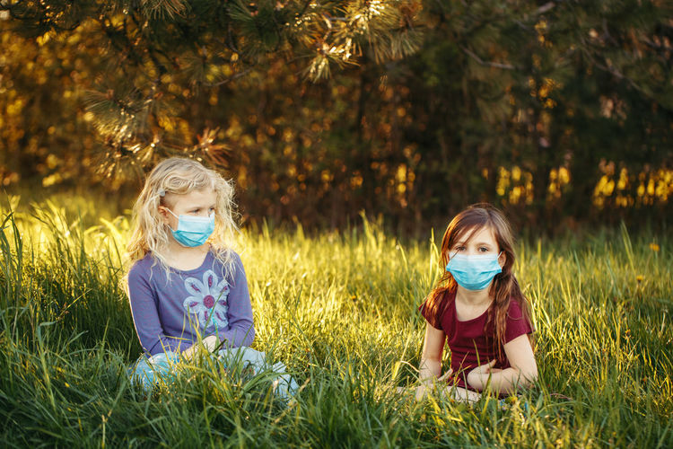 Cute girl wearing flu mask sitting on grass at park