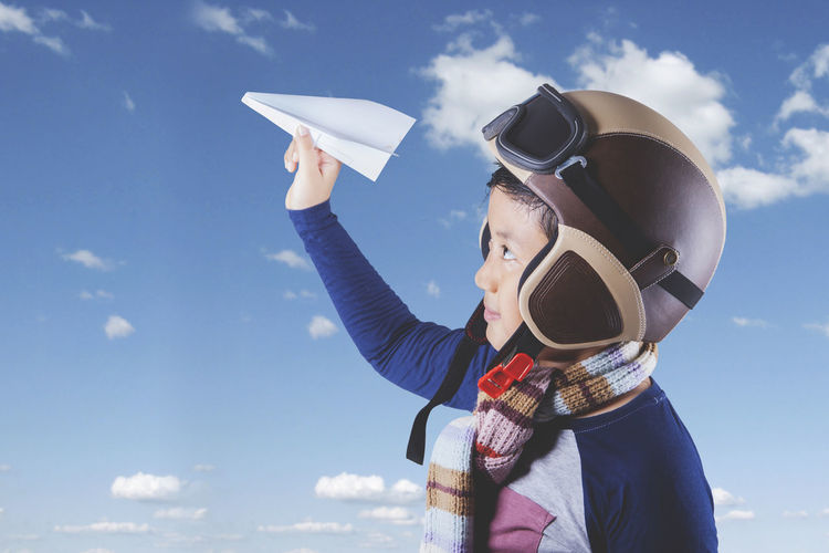 Side view of boy holding paper airplane while wearing helmet against cloudy sky