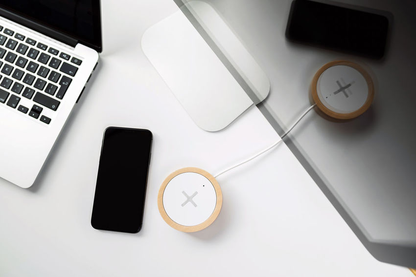 Mobile phone and wireless charger on office table. Future technology concept. Wireless Charger Office Reflection Blank Business Communication Computer Connection Drink High Angle View Indoors  Keyboard Laptop No People Office Portable Information Device Smart Phone Still Life Studio Shot Table Technology Top Down View White Wireless Technology