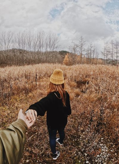 Cropped image of man holding hands with girlfriend on field against cloudy sky