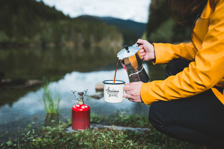 Man holding coffee by lake