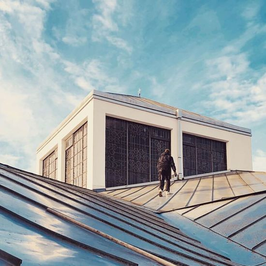 Low angle view of woman walking against building