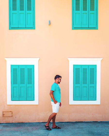 Side view of mid adult man walking against building in city