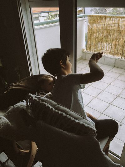 Boy sitting by window at home