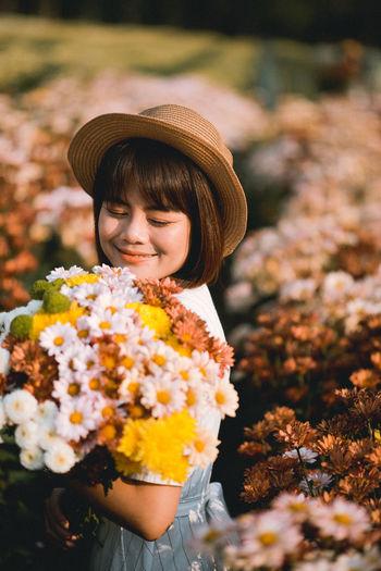 Woman wearing hat standing by flowering plants on field