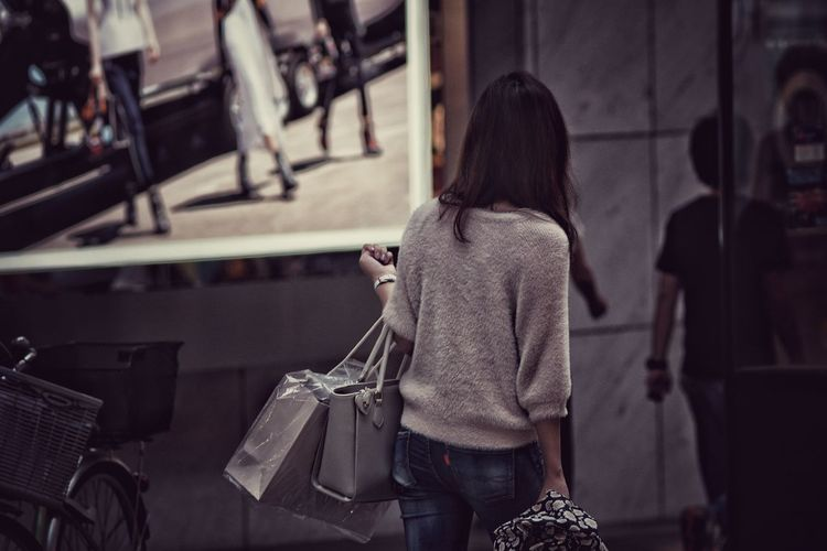Rear view of woman carrying bags while walking on street
