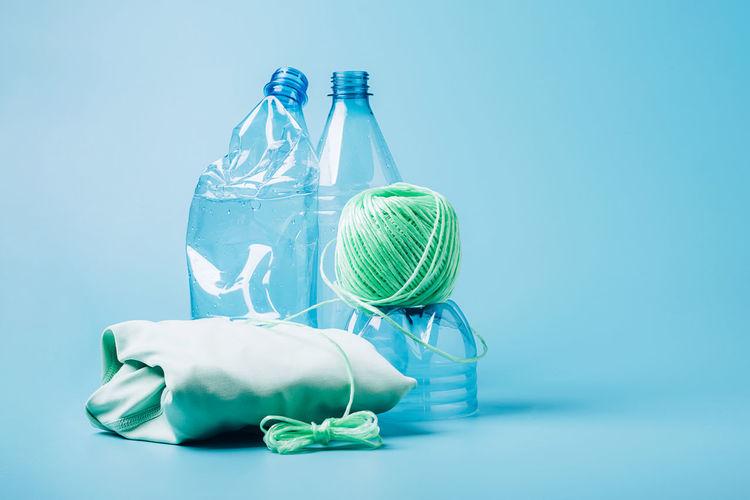 Green bottle against blue glass on table