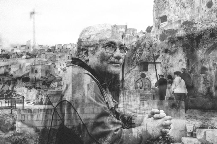 Portrait of man standing by buildings in city