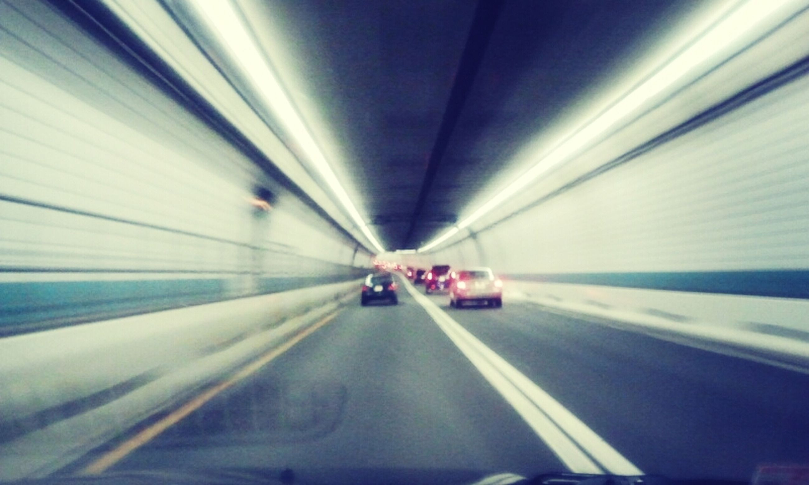 transportation, indoors, the way forward, tunnel, mode of transport, ceiling, illuminated, diminishing perspective, travel, road, vanishing point, on the move, blurred motion, road marking, land vehicle, motion, empty, lighting equipment, subway, subway station