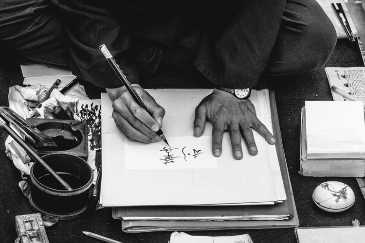 Cropped hand of man writing in paper
