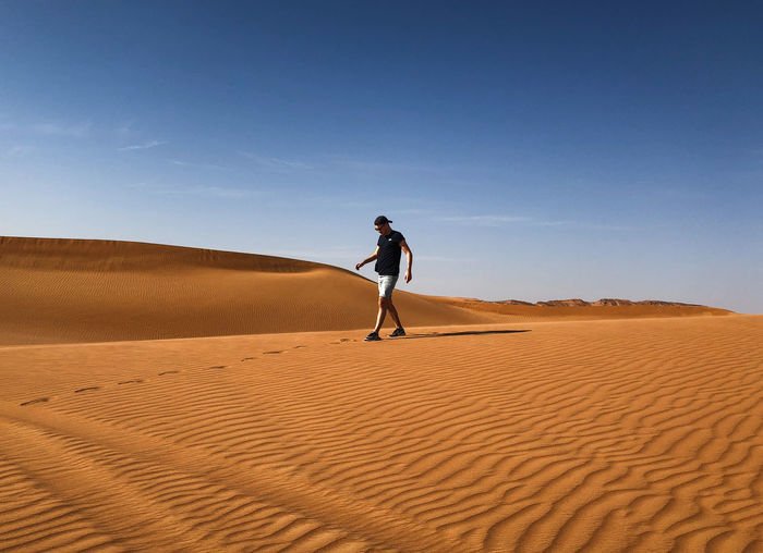 Desert Sand Land Sand Dune Scenics - Nature Landscape Climate Full Length One Person Arid Climate Sky Lifestyles Environment Nature Day Sunlight Leisure Activity Tranquil Scene Beauty In Nature Non-urban Scene Outdoors Dubai Alone Emirates