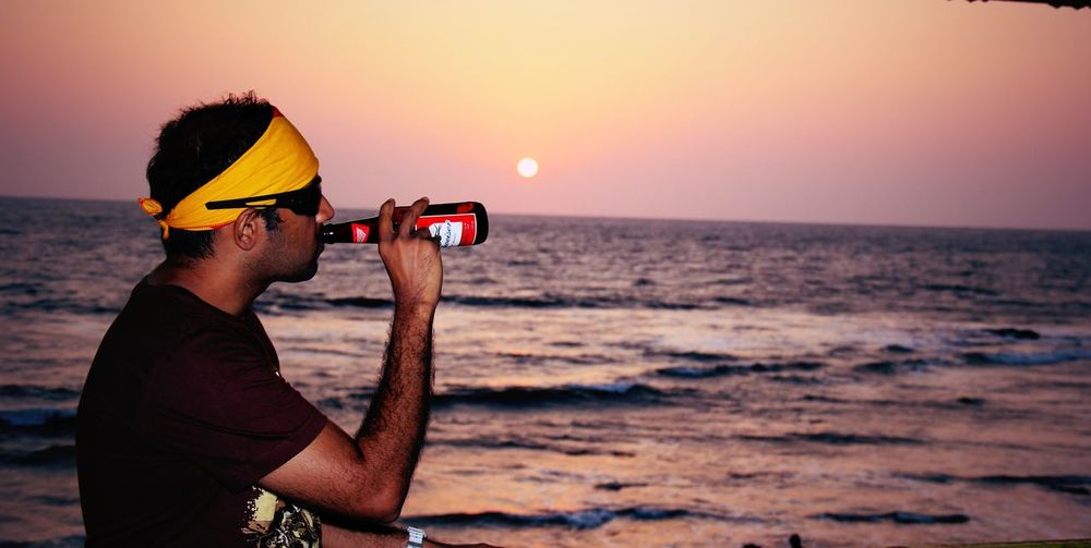 Side view of man drinking beer at beach during sunset