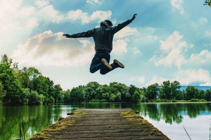 Full length of man jumping on pier over lake against sky