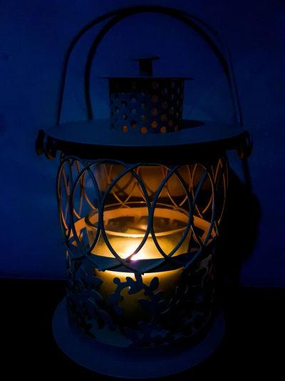 Close-up of illuminated lamp against blue sky