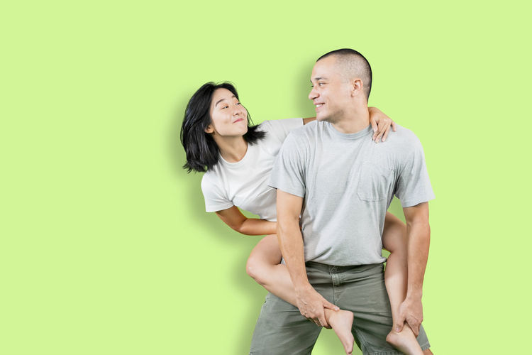 Young couple standing against green background