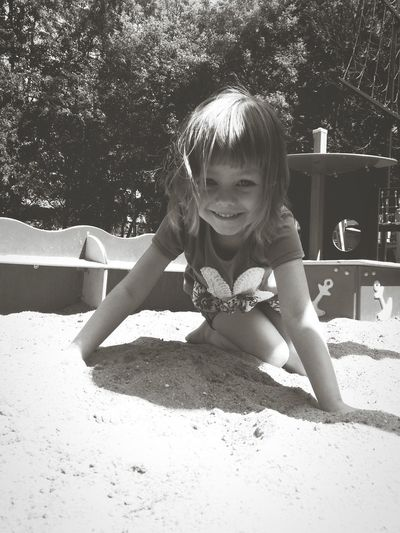 Portrait of cute girl playing in sandbox at playground