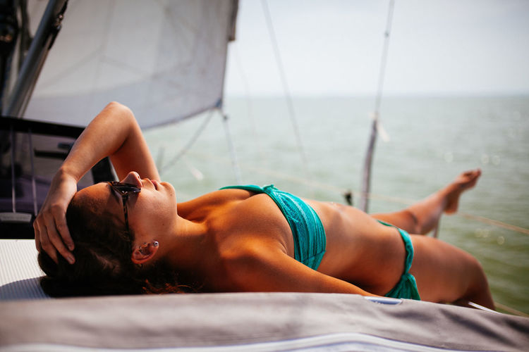 On a boat Bikini Boat Casual Clothing Day Focus On Foreground Holding Horizon Over Water Leisure Activity Lifestyles Lying Down Relaxation Sailing Scenics Sea Swimwear Tanning TeamCanon Tourism Tranquil Scene Tranquility Vacations Young Adult People And Places
