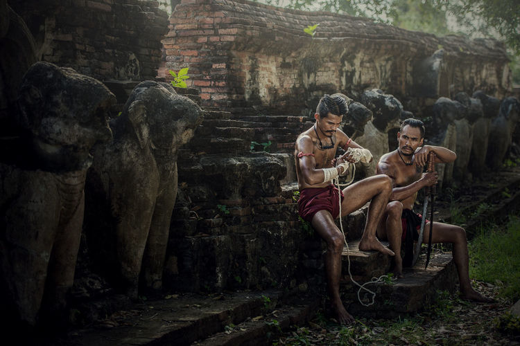 Shirtless Warriors Sitting On Steps On Old Ruin