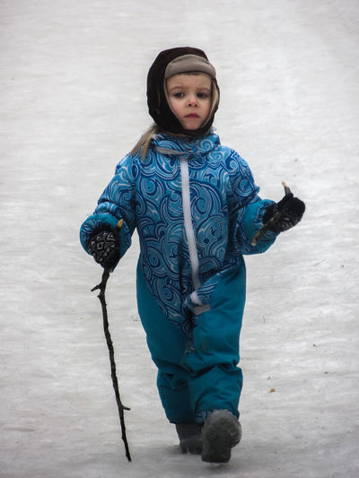 Portrait of girl holding stick walking on snow covered field