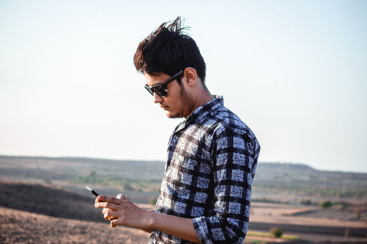 One Person Young Men Wireless Technology Technology Glasses Young Adult Mobile Phone Real People Smart Phone Focus On Foreground Casual Clothing Portable Information Device Nature Clear Sky Telephone Communication Sky Copy Space Holding Standing Outdoors Fashion