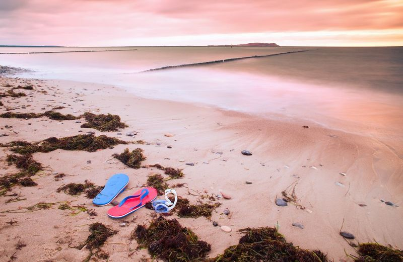 Blue red flip flops and white swimming goggles ready for using on stony beach at wooden breakwater