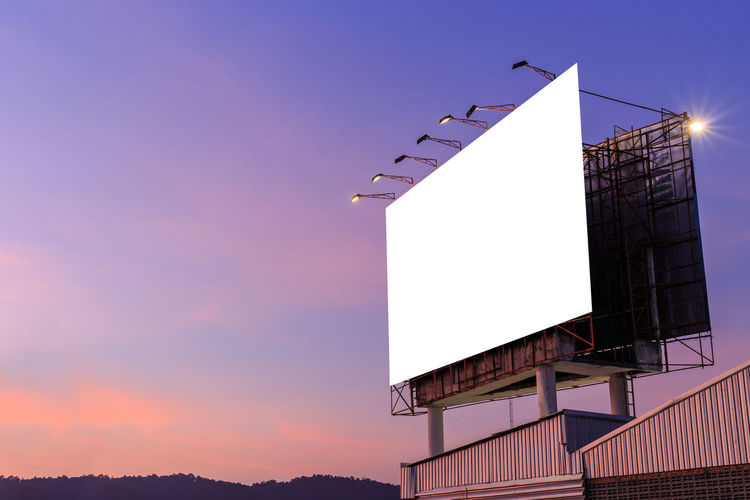 Low angle view of blank billboard against sky during sunset
