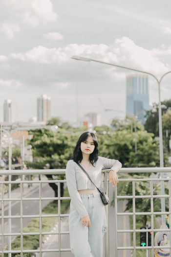 Portrait of woman standing against railing in city