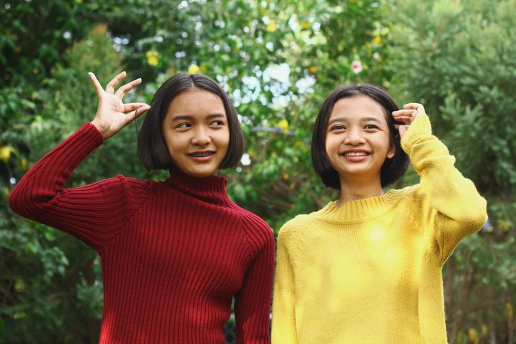 Smiling teenage friends looking away while standing against plants