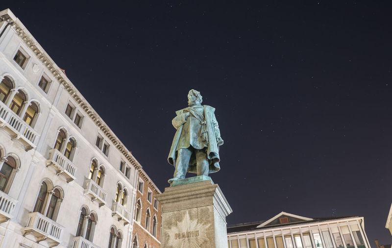 Low angle view of statue against building at night