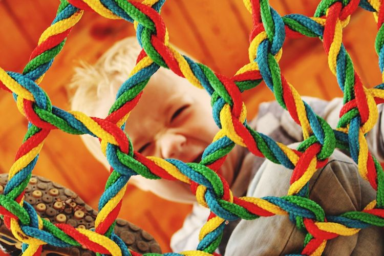 Boy seen through multi colored netting