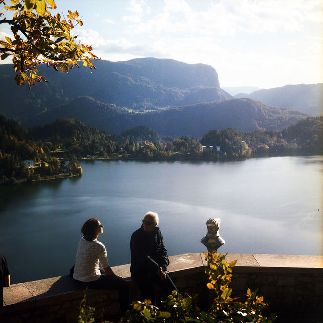 Bled Bled Castle Bled Lake Slovenia Admiring The View Afternoon Sun Autumn🍁🍁🍁 Beauty In Nature Bled, Slovenia Catching Sunrays Film Photography Friendship Lake Mountain Mountain Range Nature Real People Rear View Scenics Sitting Sky Togetherness Tranquility Travel Destinations Water EyeEmNewHere Second Acts Be. Ready. This Is Aging