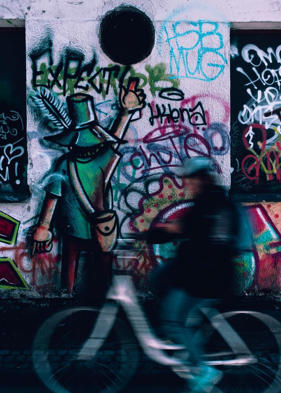 MAN WALKING WITH GRAFFITI ON WALL