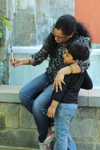 Woman taking selfie with son at retaining wall
