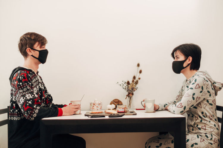 Side view of young man and woman wearing mask sitting at cafe