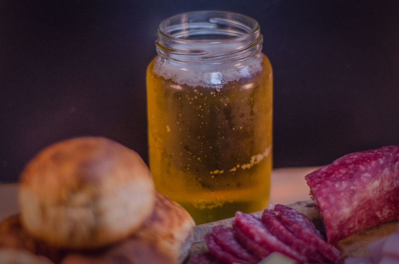 Close-Up Of Beer In Jar With Bread And Sliced Salami On Table