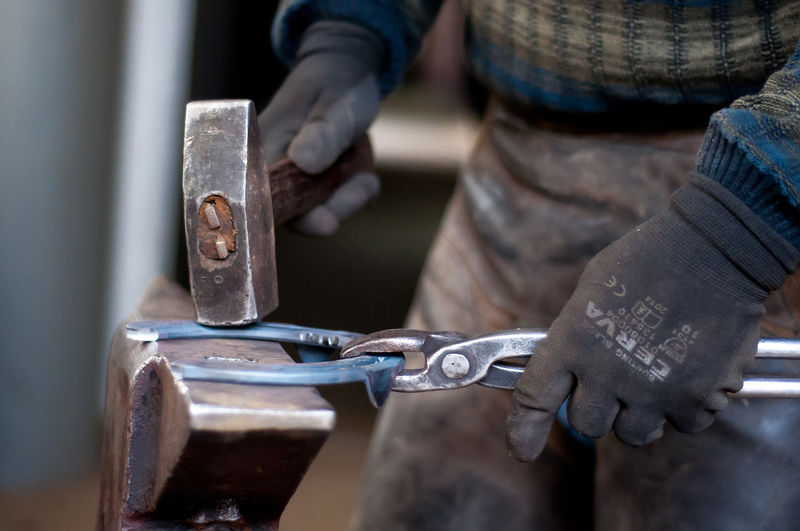 Cropped Image Of Person Making Horseshoe In Workshop