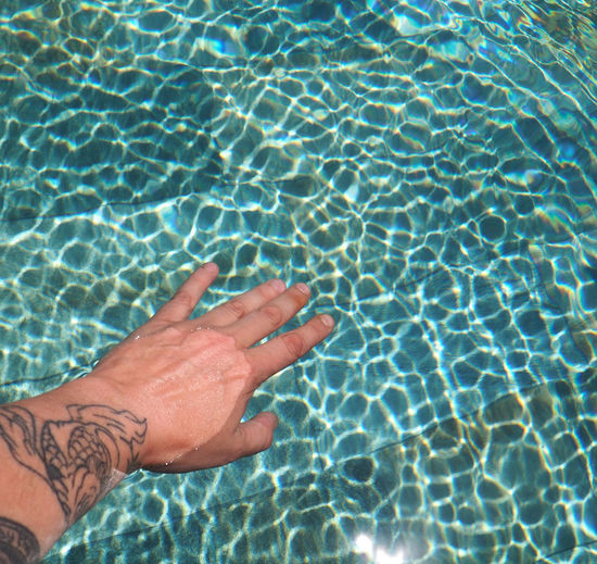 High angle view of woman tattooed hand in swimming pool