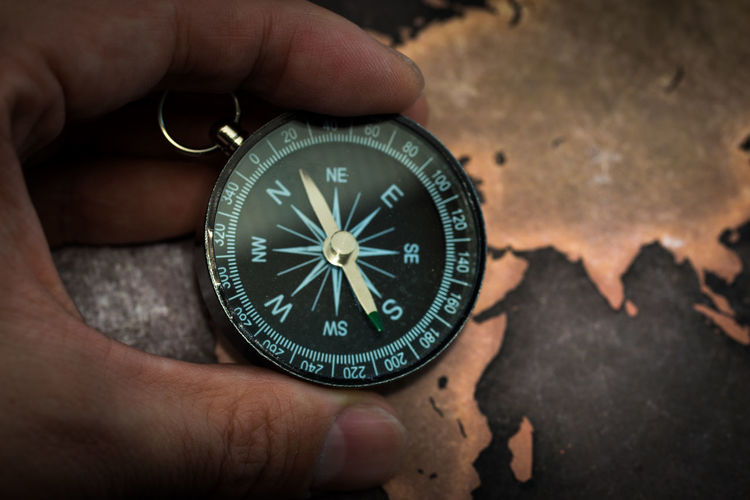 Cropped hand holding compass against world map