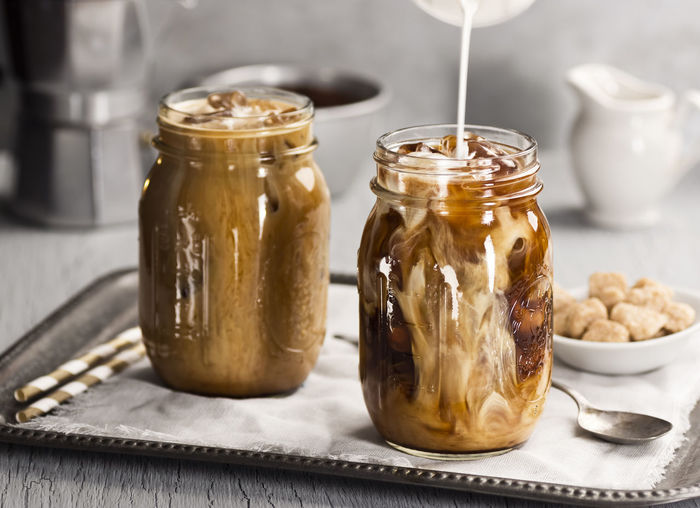 Milk Pouring into Glasses of Iced Coffee on a Metal Tray with Sugar and Straws in the background Beverage Blending Caffeine Coffee Drinks Ice Iced Coffee Liquid Mason Jar Pouring Sugar Tray Cold Cold Drink Cream Drink Glass Gray Iced Metal Milk Nobody Swirling Two ıced Coffee