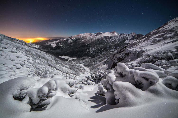 Scenic view of snow covered mountains against sky at night