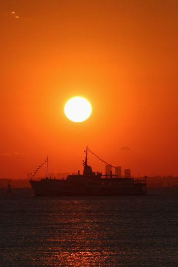 Silhouette ship on sea against orange sky during sunset
